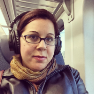 A photo of Stephanie, the chief editor. She has straight brown hair and glasses, and is wearing headphones.